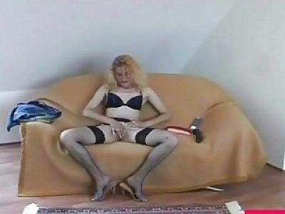 Blonde honey masturbates by using dildo on couch