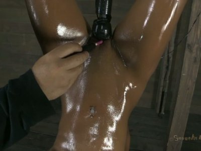Oil covered nympho gets hung upside down and gets her pussy stimulated